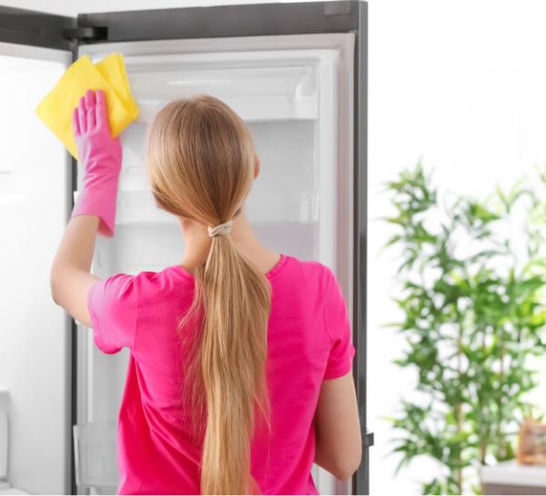 woman wiping down fridge