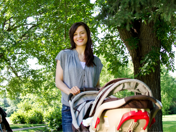 woman walking baby in the stroller after a c-section