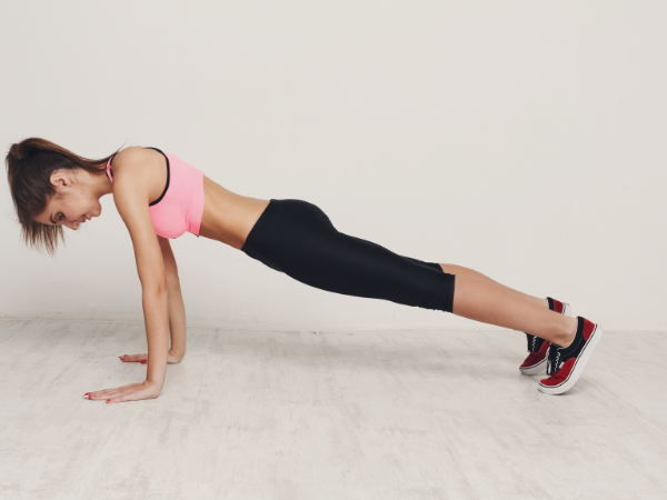 woman doing a 60 second plank  for a 20 minute cardio workout
