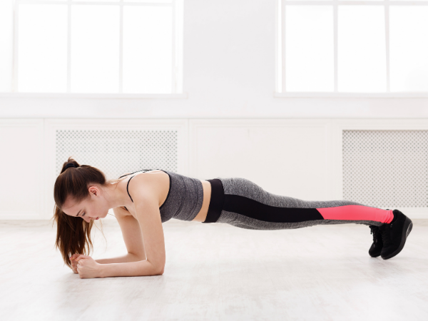 woman doing a plank on her elbows for a five minute plank challenge