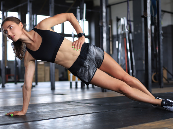 woman doing a side plank for a beginner plank challenge